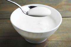 Iogurte branco em uma colher e em uma bacia fotos de stock