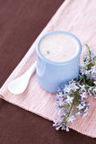 Iogurte caseiro em uma bacia cerâmica em uma toalha de mesa cor-de-rosa, em uma colher branca e em um ramo do lilás Imagens de Stock