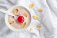Iogurte, cereja vermelha, milho secado e colher na bacia branca na toalha de mesa branca foto de stock royalty free