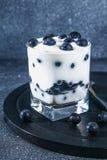 Iogurte com as bagas azuis da ameixoeira-brava em um vidro Framboesa do gelado da baga dessert fotografia de stock