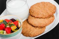 Iogurte com as cookies da salada e da aveia de fruto na placa no fundo de madeira escuro Pequeno almoço saudável fresco fotografia de stock royalty free