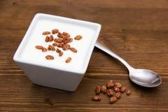 Iogurte com cereal do arroz na madeira Imagens de Stock Royalty Free