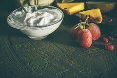 Iogurte com frutos, com fundo escuro imagens de stock royalty free