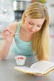Iogurte comer da jovem mulher e livro de leitura Imagem de Stock