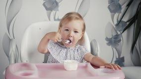 Iogurte comer da menina na cozinha, alimento pequeno da criança do bebê, criança que come com colher Fotografia de Stock Royalty Free