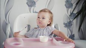 Iogurte comer da menina na cozinha, alimento pequeno da criança do bebê, criança que come com colher video estoque