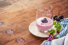 Iogurte da cereja e cereja madura com um ramo de Imagem de Stock Royalty Free