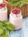 Iogurte da framboesa em uma tabela de madeira imagem de stock