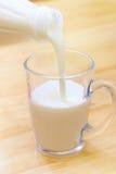 Iogurte de derramamento em um vidro fotos de stock
