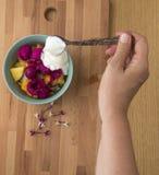 Iogurte de derramamento em uma bacia de frutos foto de stock