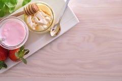 Iogurte e coalho com mel na placa na tabela de madeira Imagem de Stock