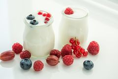 Iogurte e várias bagas em um fundo claro Foto de Stock