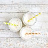 Iogurte em três frascos pequenos com palhas Imagens de Stock Royalty Free