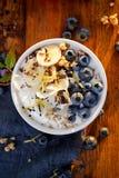 Iogurte natural com os mirtilos, as bananas e o muesli orgânicos da adição imagens de stock royalty free