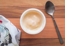 Iogurte no fim plástico do copo acima com a colher de prata pequena, vista superior fotografia de stock royalty free