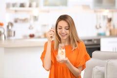 Iogurte saboroso comer atrativo novo da mulher na cozinha foto de stock