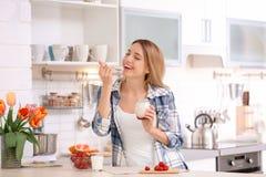 Iogurte saboroso comer atrativo novo da mulher na tabela imagem de stock royalty free