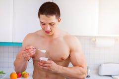 Iogurte saudável do homem novo comer na ruptura do halterofilista da cozinha imagem de stock