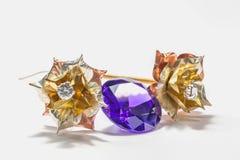 Iolite smokey blue on white background. Smokey blue diamond with golden flowers Stock Photo