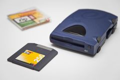 Iomega Zip 250 Drive and Disk. Iomega Zip 250 SCSI Drive and Disk, with jewel case out of focus and white background Stock Photo