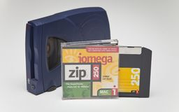 Iomega Zip 250 Drive and Disk. Iomega Zip 250 SCSI Drive, Disk and jewel case on white background Stock Photography