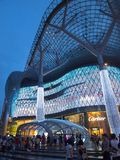 ION Orchard Architecture. A side view of ION Orchard, Singapore captures the curvy structure of the landmark shopping mall at dusk where a crowd gathers during Stock Images
