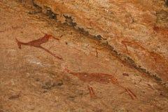 Ione africano delle montagne delle pitture antiche della roccia un fondo beige Fotografia Stock Libera da Diritti