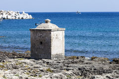 Ionian Sea. Small cubical building on the rocks. Blue sea. Ionian Sea (Mediterranean Sea). An old small cubical building on the rocks near the blue sea. Santa Stock Photos