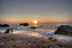 Ionian Sunset. Sunset is reflecting in Ionian sea highlighting wet rocks and pebbles Stock Images