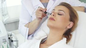 Iontophoresisrol van Cosmetologistbewegingen langs cliënt` s voorhoofd stock videobeelden