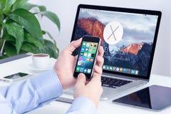 与iOS 9的苹果计算机iPhone在男性手和Macbook赞成视网膜上 免版税库存照片