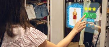 Iot聪明的零售未来派技术概念,使用与真正或被增添的现实的聪明的显示的愉快的女孩尝试在商店 免版税图库摄影