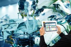 Iot industry 4.0 concept,industrial engineer using software augmented, virtual reality in tablet to monitoring machine in real t. Ime.Smart factory use Royalty Free Stock Photos