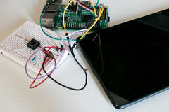 IoT prototype circuit with single board connected to a tablet. And controlled by a circuit made on a breadboard activated bya button. Maker prototipe for Royalty Free Stock Photography