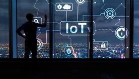IoT security theme with man by large windows at night. IoT security theme with man writing on large windows high above a sprawling city at night royalty free stock photo
