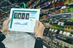 Iot smart retail in the futuristic concept, the retailer hold the tablet and use augmented reality technology monitor data of out. Of shelve, price, planogram stock photo