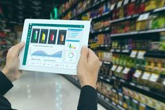 Iot smart retail in the futuristic concept, the retailer hold the tablet and use augmented reality technology monitor data of out. Of shelve, price, planogram royalty free stock photos