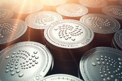 IOTA coins in blurry closeup with sunburst from above. IOTA growth concept. 3D rendering Stock Image