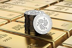 IOTA coins laying on stacked gold bars gold ingots rendered with shallow depth of field. Stock Images