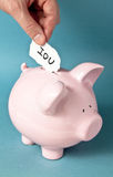 IOU note. Hand placing an IOU note in a piggy bank Royalty Free Stock Photos