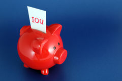 IOU Piggy Bank. IOU card in piggy bank signifying debt or financial problems Royalty Free Stock Image