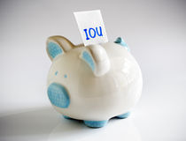 IOU Piggy Bank. IOU note in piggy bank signifying debt or financial problems Royalty Free Stock Image
