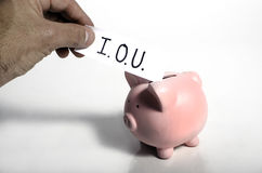 An IOU into a piggy bank. An IOU slip being placed into a piggy bank Royalty Free Stock Image