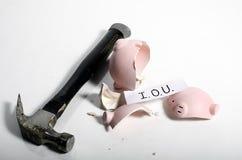 An IOU into a piggy bank. An IOU slip showing inside a broken piggy bank Royalty Free Stock Photography