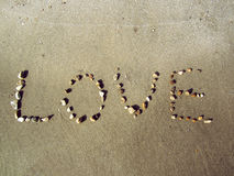 Iove on beach. Word love on the beach,stones create word of love on beach sand in day light Royalty Free Stock Image
