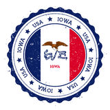 Iowa flag badge. Grunge rubber stamp with Iowa flag. Vintage travel stamp with circular text, stars and USA state flag inside it. Vector illustration Stock Image
