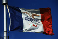 Iowa State Flag. This is the Iowa State flag, waving in the wind. It is on a flagpole against a blue sky. There are three colors on the flag, the center stock images