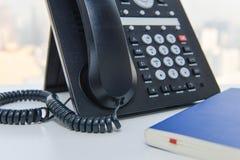 IP电话和蓝色笔记本 免版税库存图片