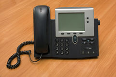 IP Phone. Dual channel IP phone on wooden table Royalty Free Stock Photo