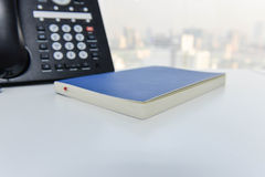 IP Phone and blue notebook on the white table Royalty Free Stock Images